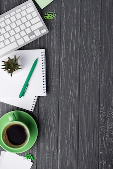Vista superior del escritorio de madera con taza de café y papelería