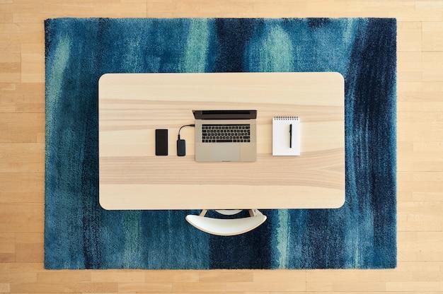 Vista superior del escritorio moderno en alfombra de diseño azul.