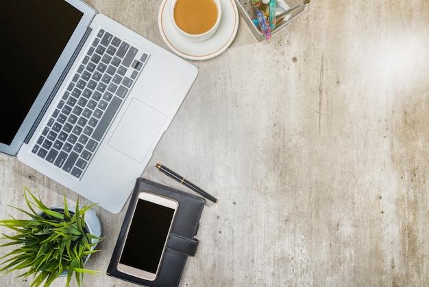 Vista superior del escritorio de negocios con computadora portátil, teléfono móvil, café, macetas, notebook y accesorios de negocios