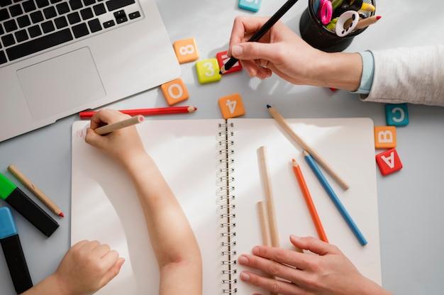 Vista superior del escritorio con el niño siendo tutorizado