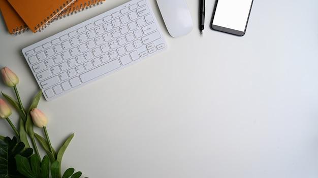 Vista superior del escritorio de oficina blanco con teléfono inteligente, teclado y espacio de copia.