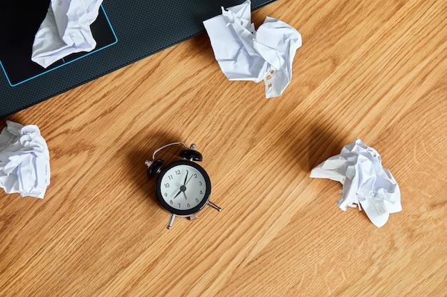 Vista superior del escritorio de oficina de madera con reloj, cuaderno, bolas de papel arrugadas, cambio de mentalidad, plan b, tiempo para establecer nuevos objetivos, planes, concepto de gestión del tiempo, endecha plana.