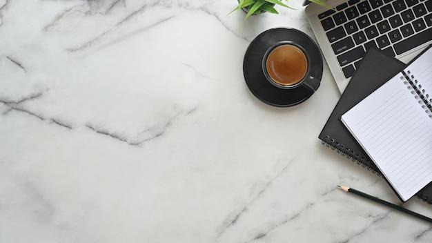 Vista superior escritorio de oficina mesa de mármol con laptop, papel de cuaderno, lápiz y café exprés.
