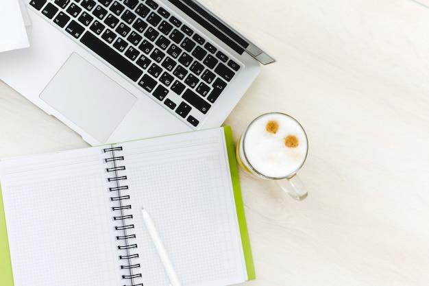 Vista superior del escritorio de oficina con ordenador portátil, portátiles y taza de café sobre fondo de color blanco. mesa de oficina con cuaderno en blanco y portátil
