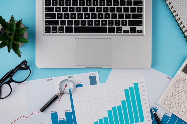 Vista superior del escritorio de oficina con tabla de crecimiento y dispositivo portátil