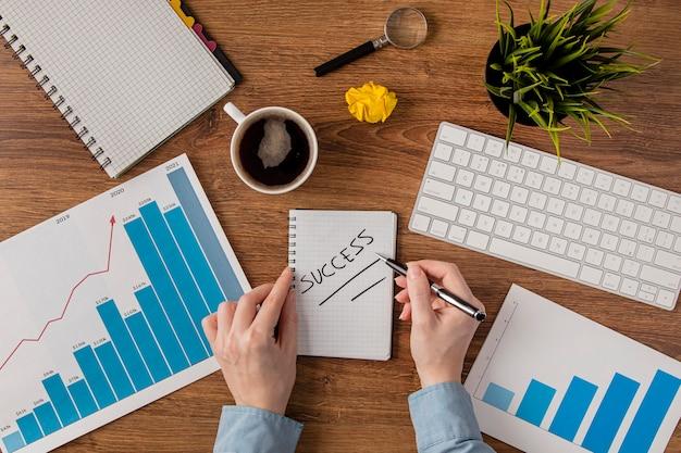 Vista superior del escritorio de oficina con tabla de crecimiento y manos escribiendo éxito