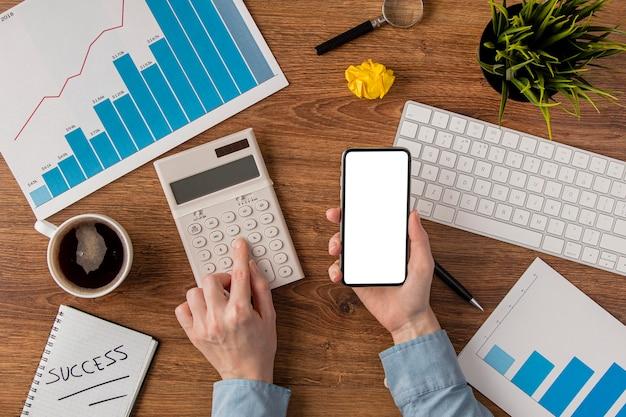 Vista superior del escritorio de oficina con tabla de crecimiento y manos usando calculadora