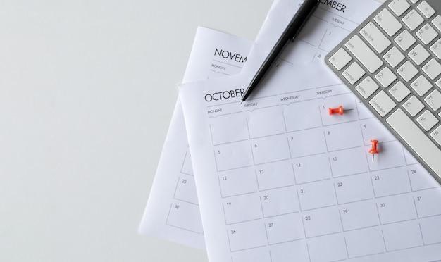 Vista superior del escritorio de oficina con teclado y horario de trabajo