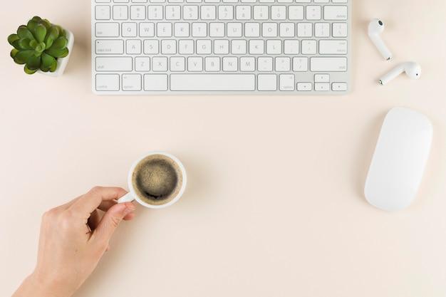 Vista superior del escritorio con teclado y mano sosteniendo la taza de café