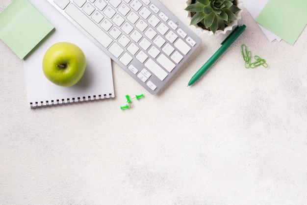 Vista superior del escritorio con teclado y manzana