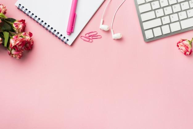 Vista superior del escritorio con teclado y ramo de rosas