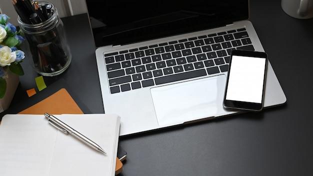Vista superior del escritorio de trabajo con accesorios que se colocan en él computadora portátil, pantalla en blanco móvil, notas, bolígrafo y portalápices.