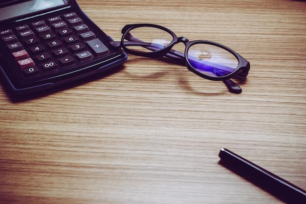 Vista superior del escritorio de trabajo con anteojos, pluma, ordenador portátil, tableta, ratón, reloj despertador, calculadora y maqueta de papel.