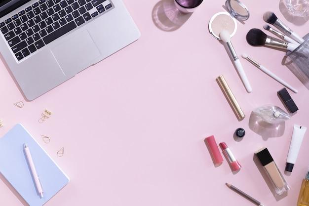 Vista superior del escritorio de trabajo de blogger de belleza de mujer con computadora o computadora portátil, cuaderno, cosmética decorativa, deja sombras y luz dura, sobre en mesa de color rosa y blanco pastel. fondo plano laico.