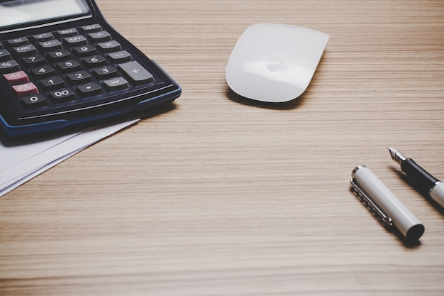 Vista superior del escritorio de trabajo con maqueta de papel pluma, portátil, tableta, ratón, calculadora y gráfico.
