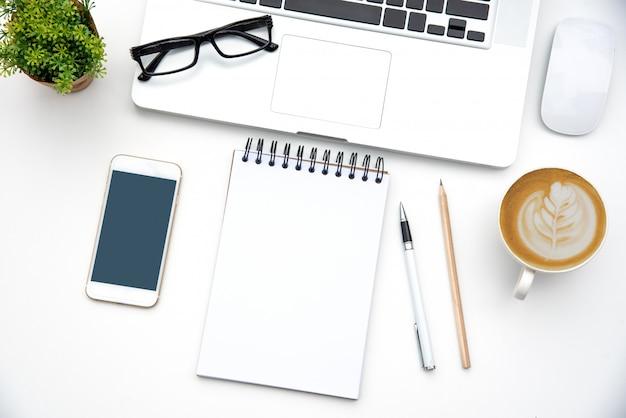 Vista superior con escritorio de trabajo con ordenador portátil, teléfono móvil, taza de café lápiz portátil y anteojos en la oficina.
