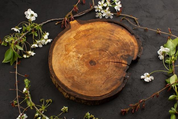 Vista superior escritorio vacío de madera junto con flores blancas sobre el fondo oscuro