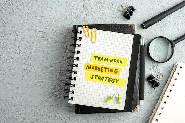 Vista superior de los escritos de marketing de estrategia de trabajo en equipo en hojas de colores en cuaderno espiral y lupa de libro sobre fondo de arena gris