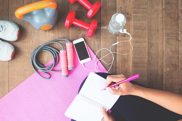 Vista superior de la escritura deportiva de la mujer en el cuaderno, planeando entrenamiento