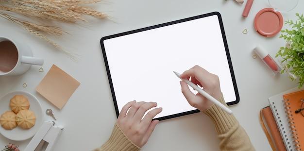 Vista superior de la escritura femenina joven en tableta de pantalla en blanco en concepto de espacio de trabajo femenino beige cálido con maquillaje
