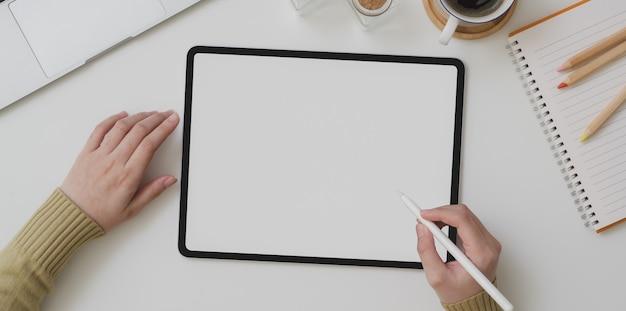 Vista superior de la escritura femenina joven en tableta de pantalla en blanco mientras trabajaba en su proyecto