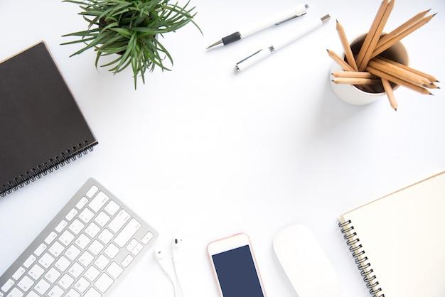 Vista superior con espacio de copia, escritorio de trabajo con ordenador portátil, teléfono celular, lápiz de cuaderno y café