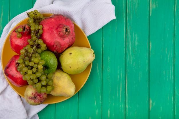 Vista superior del espacio de copia granadas con peras, manzanas y uvas en un plato sobre una pared verde