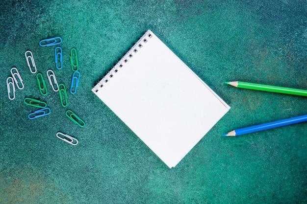 Vista superior espacio de copia lápices de color verde claro y azul con clips y bloc de notas sobre un fondo verde