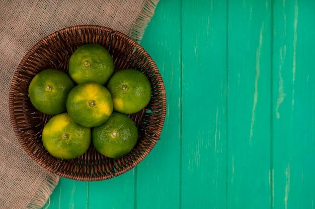 Vista superior espacio de copia mandarinas en canasta en servilleta beige en pared verde