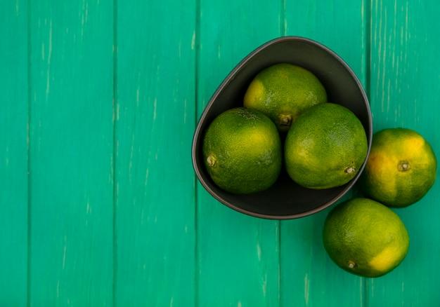 Vista superior espacio de copia mandarinas en un recipiente sobre una pared verde