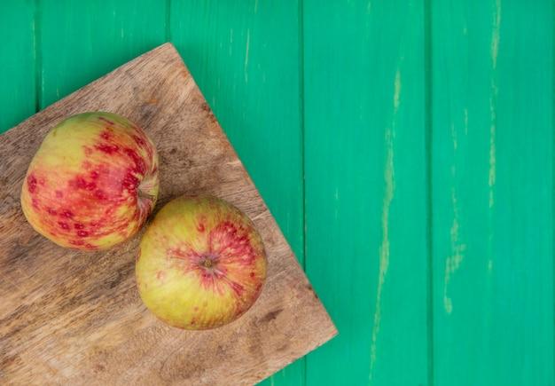 Vista superior espacio de copia manzanas en tabla de cortar en pared verde