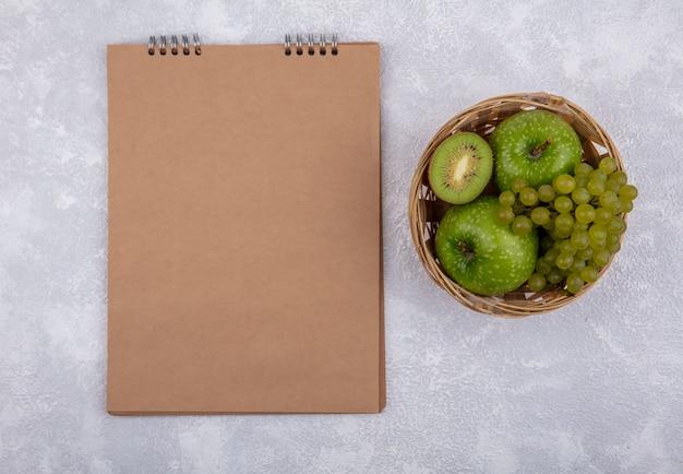 Vista superior espacio de copia manzanas verdes con uvas verdes y cuña de kiwi en canasta con bloc de notas marrón sobre fondo blanco.