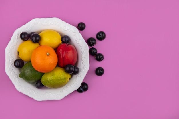 Vista superior espacio de copia naranja con limones limas ciruelas cereza y melocotones en un plato sobre un fondo rosa