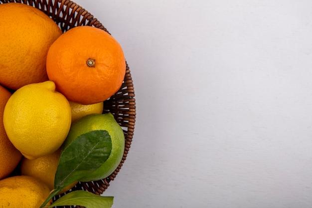 Vista superior espacio de copia pomelo con naranjas y limones en la canasta sobre fondo blanco.