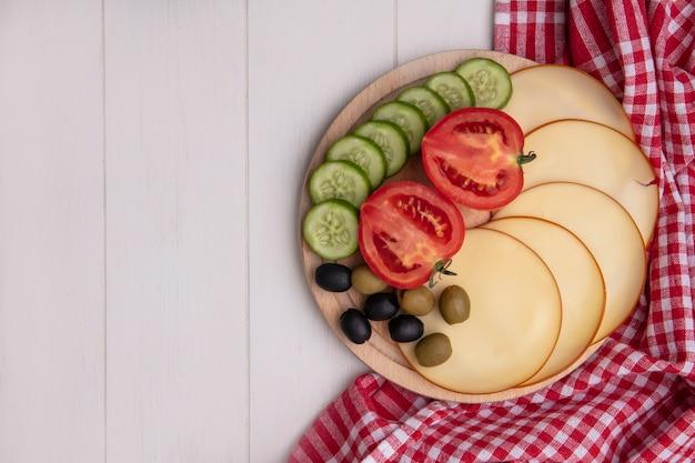 Vista superior del espacio de copia de queso ahumado con tomates, pepinos y aceitunas en un soporte con una toalla a cuadros roja sobre un fondo blanco.