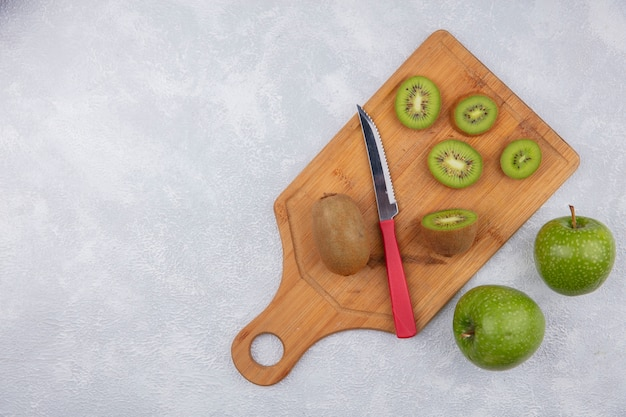 Vista superior espacio de copia rodajas de kiwi con un cuchillo en la tabla de cortar con manzanas verdes sobre fondo blanco.