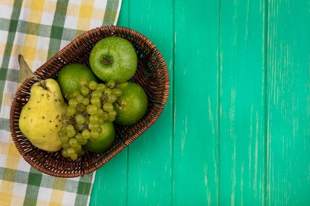Vista superior espacio de copia uvas verdes con manzana verde, mandarinas y pera en una canasta en una pared verde