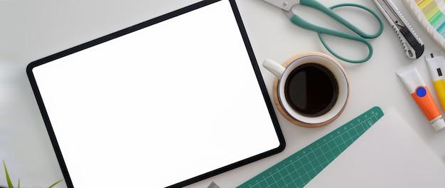 Vista superior del espacio de trabajo de arquitectura con tableta de pantalla en blanco, taza de café, tijeras y suministros