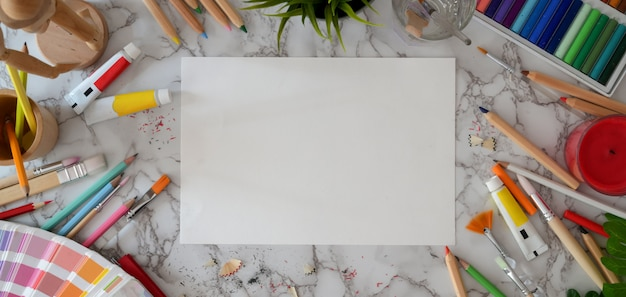 Vista superior del espacio de trabajo del artista moderno con papel de boceto y herramientas de pintura en el escritorio de mármol