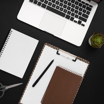 Vista superior del espacio de trabajo con bloc de notas y computadora portátil