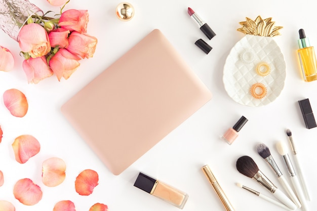 Vista superior del espacio de trabajo de blogger de moda femenina con laptop, accesorio de mujer y cosméticos en blanco.