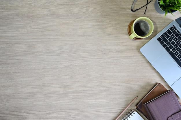 Vista superior del espacio de trabajo con computadora portátil, café, vasos, libros y decoración de plantas en la mesa de madera de la oficina.