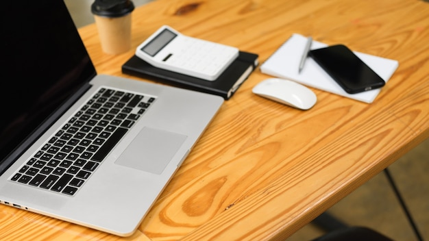 Vista superior del espacio de trabajo con computadora portátil, pantalla negra, calculadora y cosas en la mesa de madera