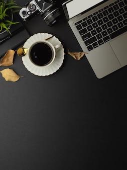 Vista superior del espacio de trabajo con computadora portátil, taza de café, cámara y espacio para copiar en la sala de la oficina en casa