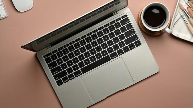 Vista superior del espacio de trabajo con computadora portátil, taza de café y suministros, ies en la sala de la oficina en casa