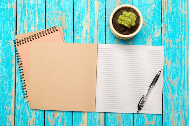Vista superior del espacio de trabajo con cuaderno en blanco y lápiz sobre fondo de mesa de madera