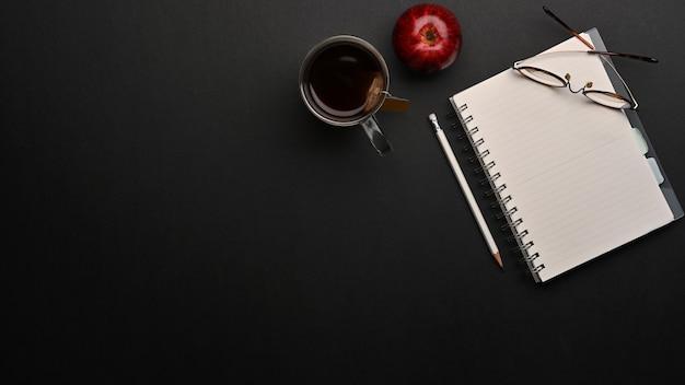 Vista superior del espacio de trabajo con cuaderno en blanco, lápiz, vasos, taza de café y espacio de copia en la oficina en casa