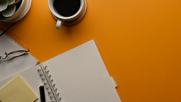 Vista superior del espacio de trabajo con cuadernos, papelería, taza de café y espacio para copiar en la sala de la oficina en casa