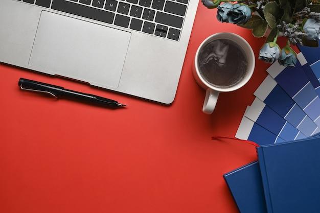 Vista superior del espacio de trabajo del diseñador creativo con computadora portátil, cuadernos de taza de café y muestra de color en rojo