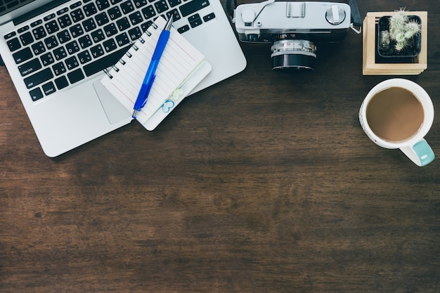 Vista superior del espacio de trabajo del escritorio de oficina con taza de café, computadora portátil, teléfono inteligente y teclado